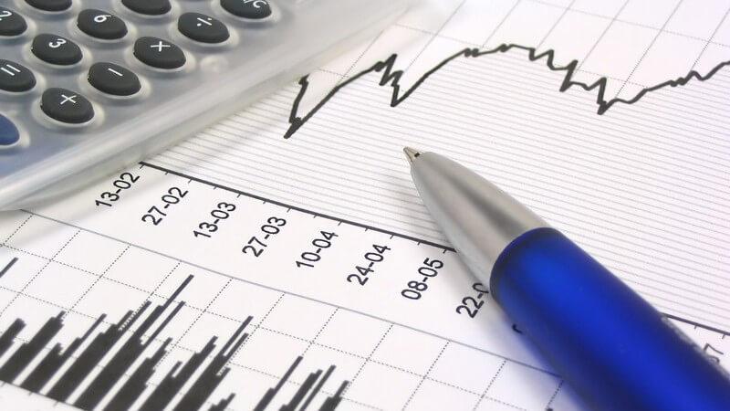 Diagramm Aktienkurve auf Tisch, daneben Kuli, Taschenrechner
