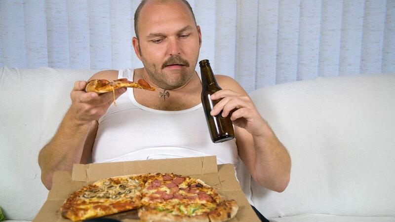 Mann im Unterhemd mit Bierflasche und Pizza auf Couch