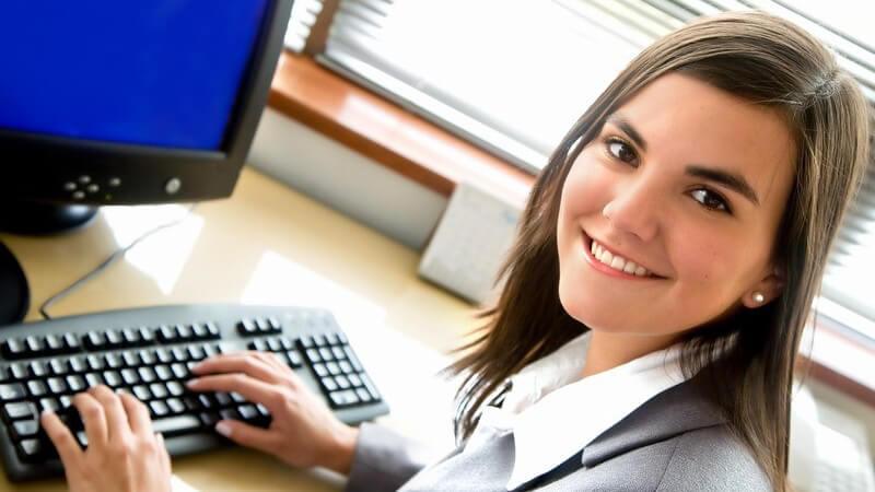Junge Geschäftsfrau im Büro sitzt vor dem Computer
