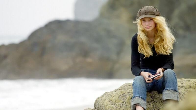Mädchen mit blonden, langen Haaren und grüner Mütze vor Bergen und See