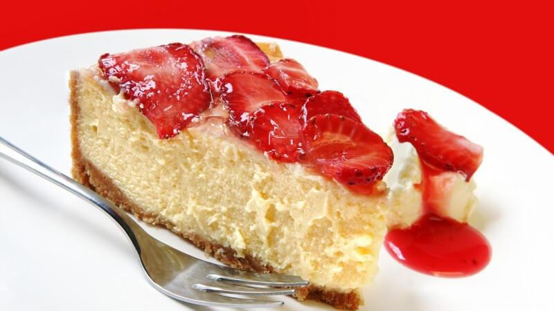Erdbeerkuchen auf weißem Teller mit Gabel vor rotem Hintergrund, ein einzelnes Stück mit Sauce daneben