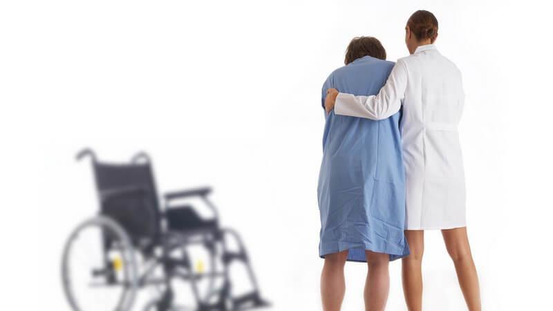 Rückenansicht, Krankenschwester stützt Patientin beim Gehen, im Hintergrund Rollstuhl