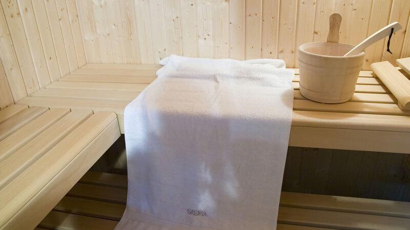 Weißes Handtuch, Aufgusseimer und -kelle auf einer Holzbank in der Sauna