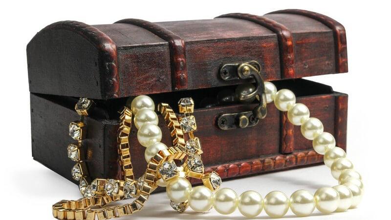 Kleine dunkelbraune Schatzkiste, aus der eine Perlenkette und Goldschmuck ragen