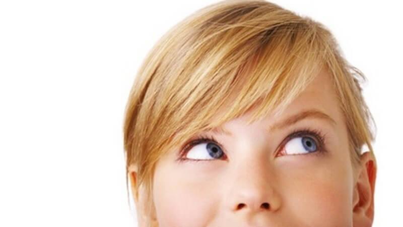 Gesicht einer blonden Frau bis unterhalb der Nase, die zum rechten oberen Bildrand schaut