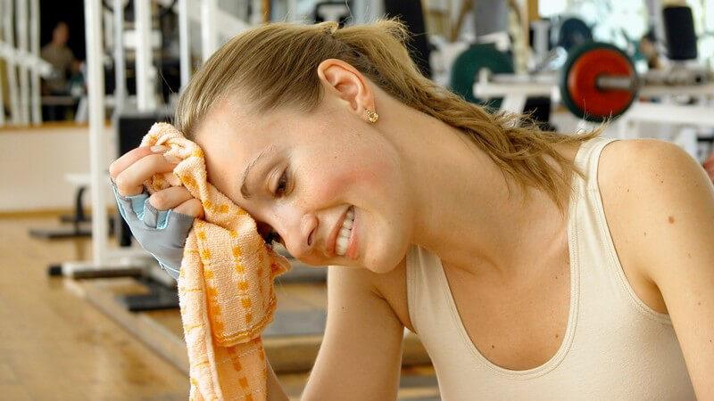 Erschöpfte Sportlerin wischt sich die Stirn und lächelt