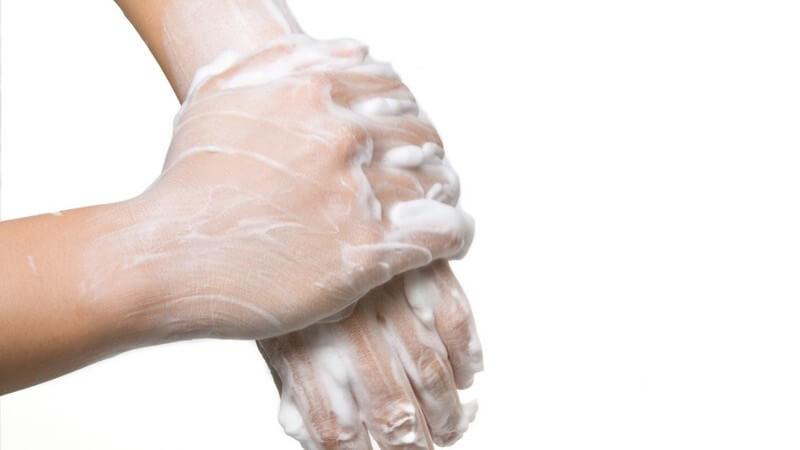 Eingeseifte Hände beim Händewaschen auf weißem Hintergrund