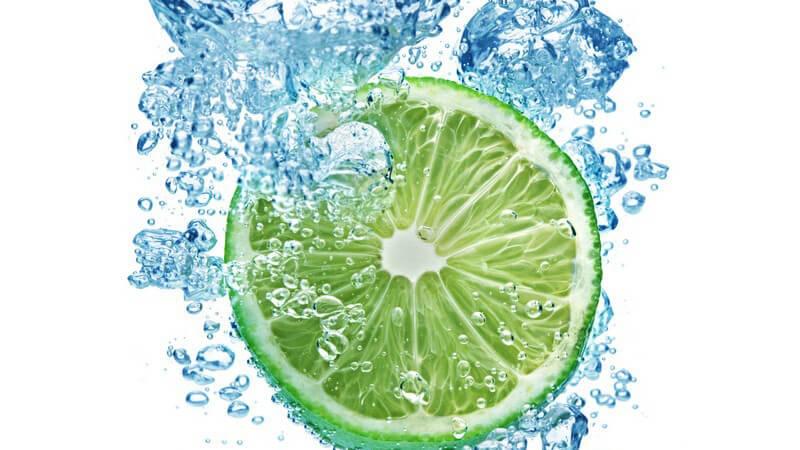 Aufgeschnittene Limette fällt ins Wasser und hinterlässt Wasserblasen unter Oberfläche