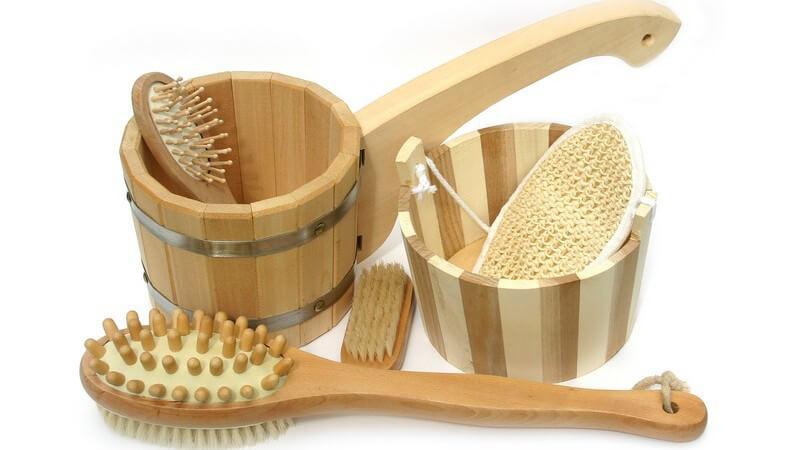 Holz Badeset mit Massagebürste, Bürsten etc in Holzeimer auf weißem Hintergrund