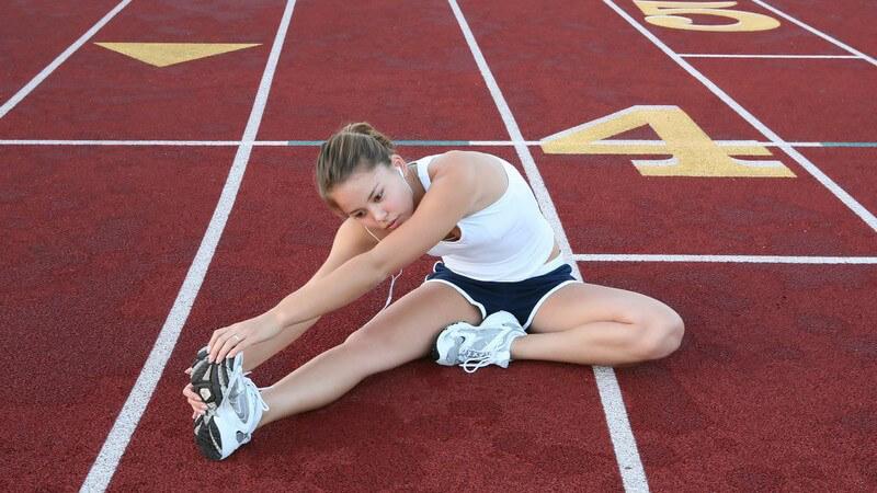 Sportlerin sitzt auf Laufstrecke und dehnt ihre Beine