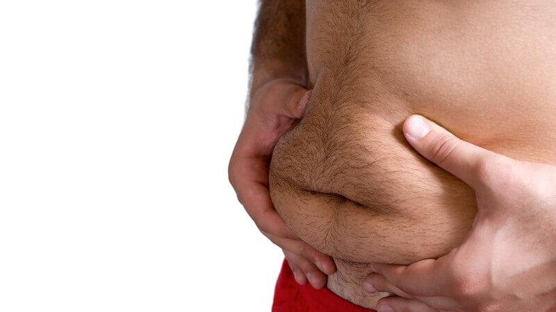 Bauch eines übergewichtigen Mannes, er drückt Bauchspeck vorne zusammen