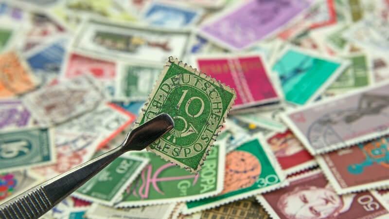 Pinzette mit grüner Briefmarke, im Hintergrund eine Briefmarkensammlung