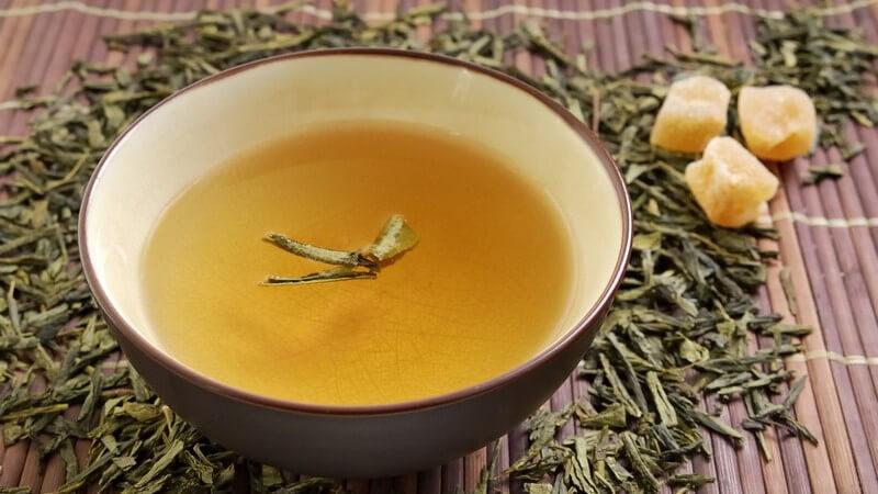 Schale mit grünem Tee auf Bastmatte mit losem Tee und Kandiszucker