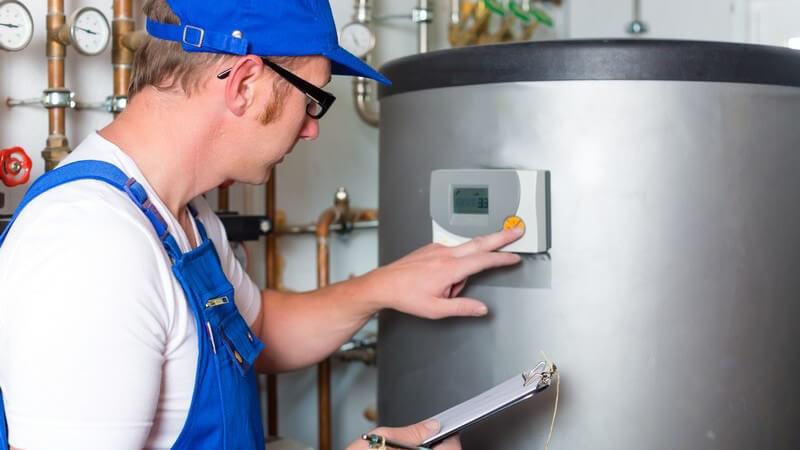 Handwerker mit blauer Mütze und Blaumann kontrolliert einen Heizungskessel