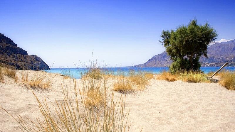 Sandstrand mit Aussicht auf das Meer und Gebirge