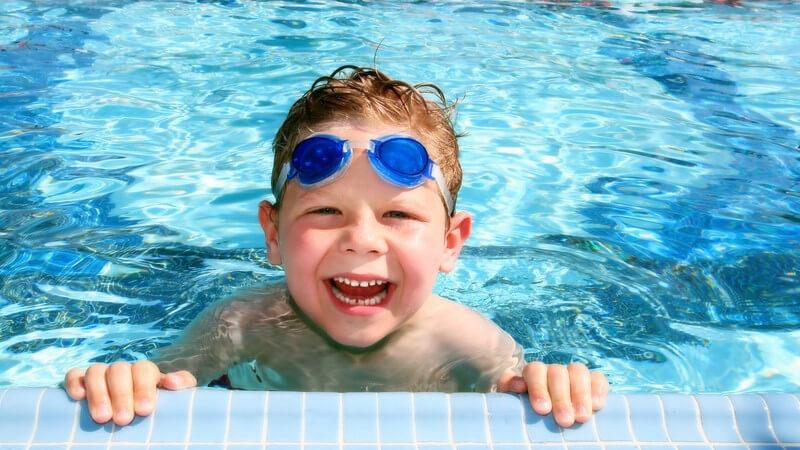 Kleiner Junge mit Schwimmbrille auf Stirn am Beckenrand im Schwimbad lacht, im Hintergrund rot-weiße Absperrleine