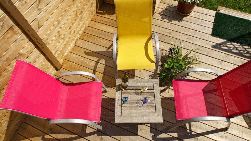 Ansicht von oben: Holztisch mit Flasche Wein und Gläsern, drei Stühle auf Terrasse