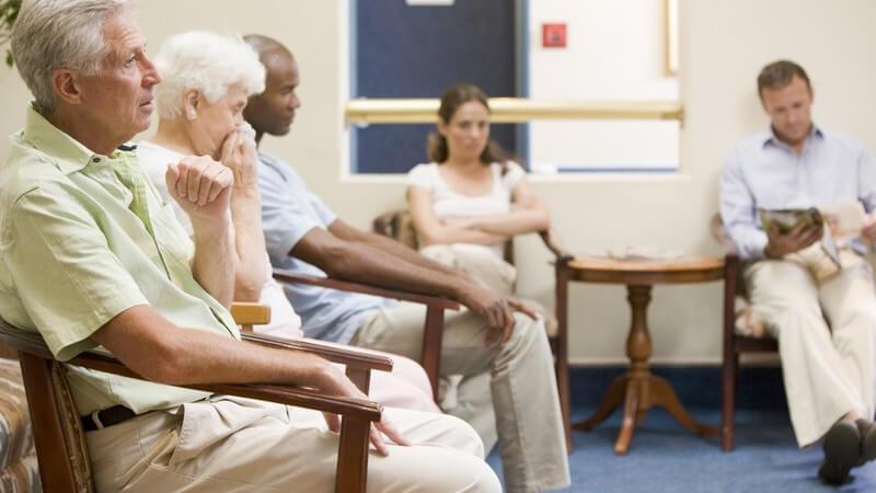 Fünf Menschen jung und alt warten im Wartezimmer
