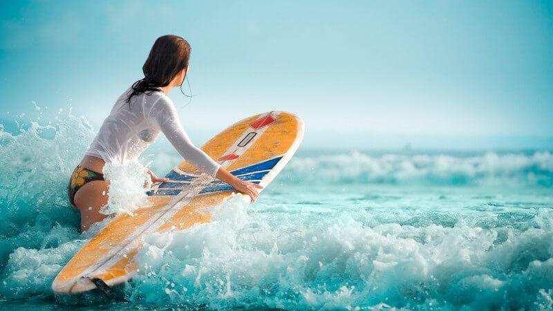 Junge Frau im Bikini und weißem, langarmigen Top steigt mit Surfbrett in die Wellen