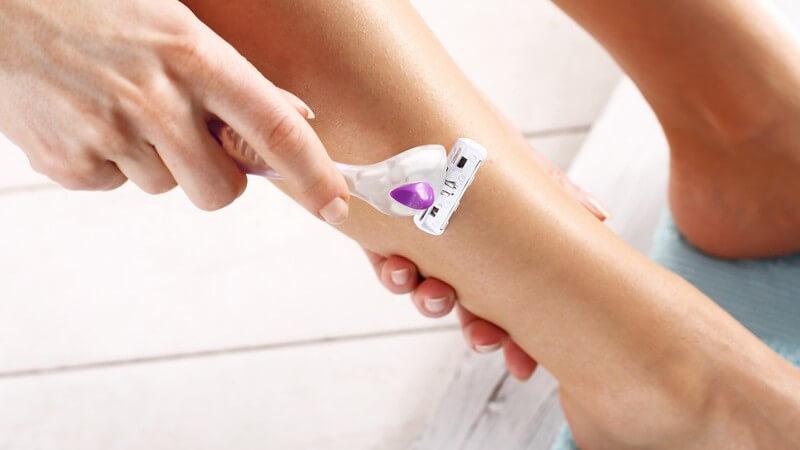 Frau rasiert sich ihr Schienbein mit einem lila-weißen Nassrasierer