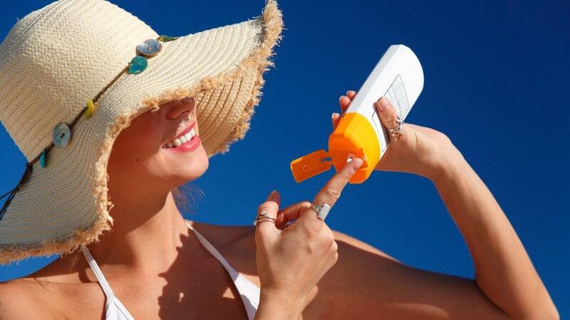 Frau mit Sonnenhut und weißem Bikini cremt sich mit Sonnencreme ein
