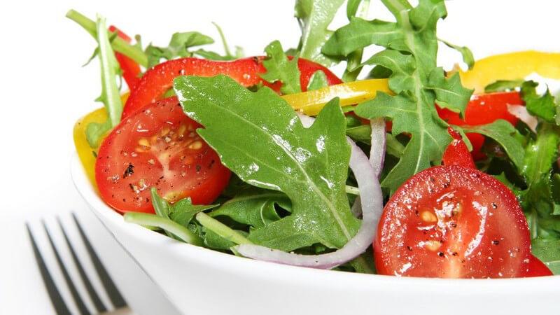 Frischer Salat mit Tomaten, Paprika, Zwiebeln in weißer Schale