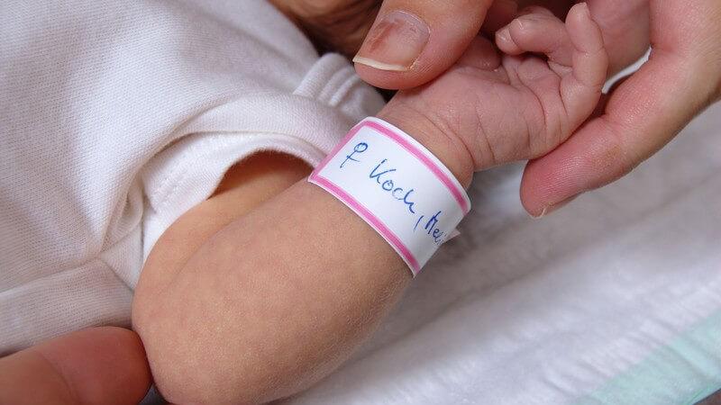 Baby kurz nach der Geburt mit einem Geburtsbändchen am Handgelenk
