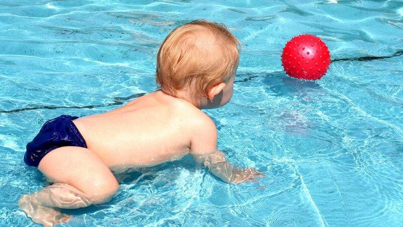 Baby spielt im Pool - Babyschwimmen