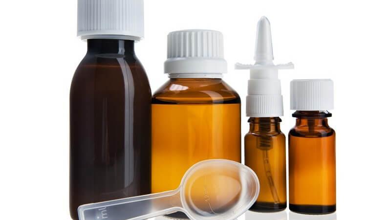 Arzneimittel - Transparenter Dosierlöffel liegt vor vier verschiedenen Medikamenten