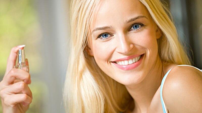 Junge lächelnde Frau trägt Parfüm auf