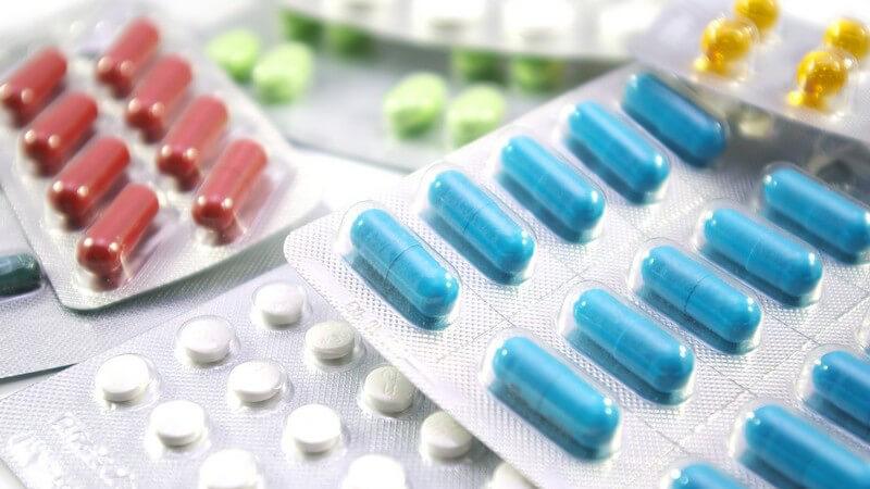 Arzneimittel - Pillenpackungen mit blauen, roten, gelben, grünen und weißen Pillen