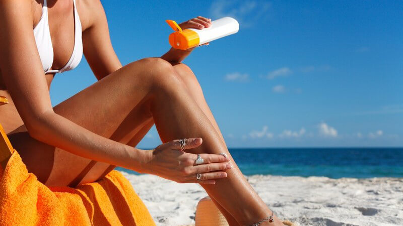 Frau am Strand in Bikini cremt sich mit Sonnencreme ein, im Hintergrund Meer