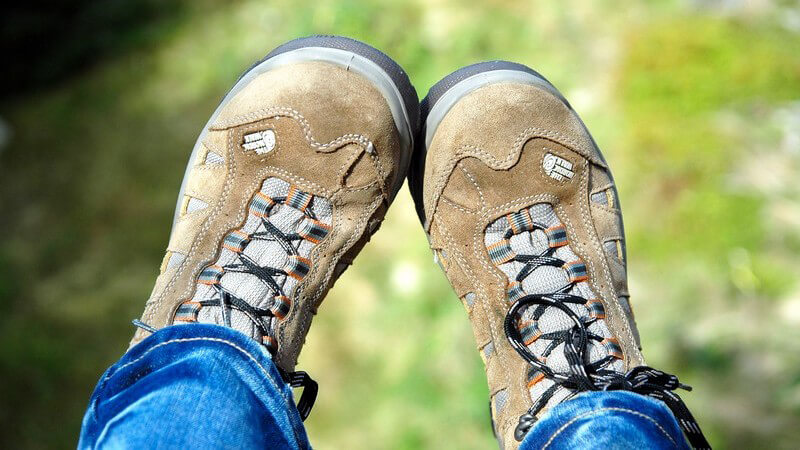 Wanderschuhe aus hellem Leder, ein Teil der Beine, im Hintergrund Wiese