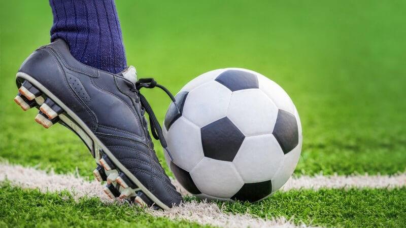 Fuß mit dunkelblauem Stutzen und schwarzem Fußballschuh schießt einen Fußball mit dem Vollspann