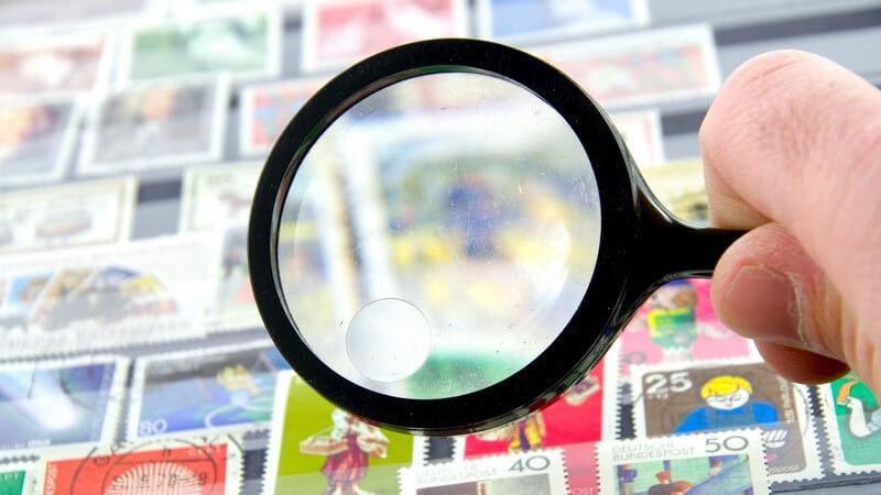 Lupe wird über Briefmarken-Sammlung gehalten