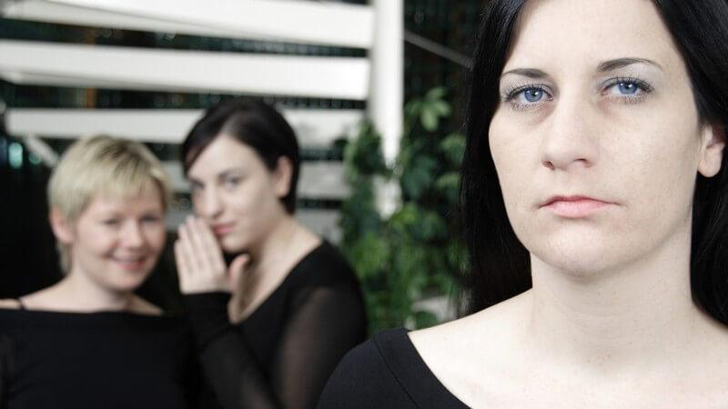 Frauen in schwarzen Oberteilen, 1 blickt in die Kamera, 2 stehen hinten, 1 flüstert der anderen ins Ohr
