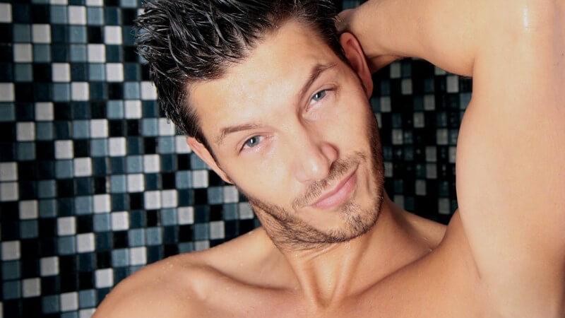 Junger, sportlicher Mann unter der Dusche, schaut in die Kamera, Kopf leicht schräg
