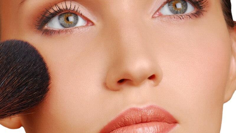 Frau mit hellem Lidschatten, grünen Augen und apricot Lippenstift hält Schminkpinsel an rechte Wange