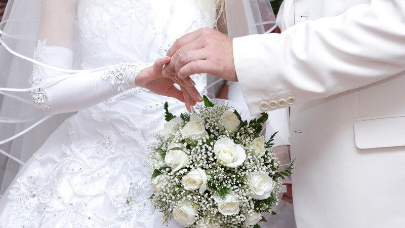 Nahaufnahme Brautpaar in weiß, Bräutigam zieht Braut den Ehering an
