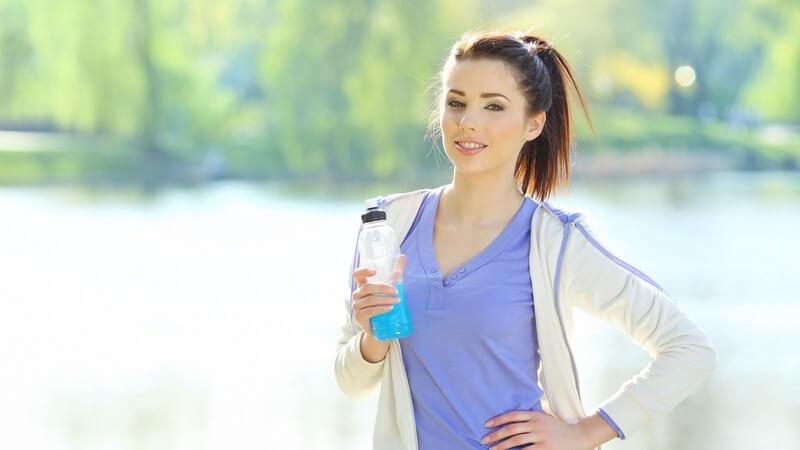 Joggerin mit Getränk im Park