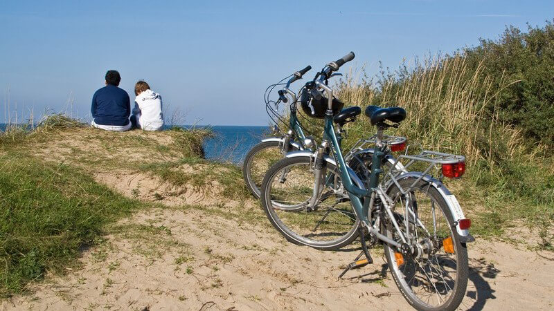 Vater und Kind sitzen am Strand, im Vordergrund Fahrräder, Pause