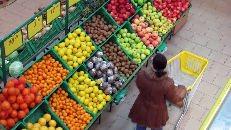 Aufnahme von oben, Frau schiebt im Supermarkt Einkaufswagen an Obstabteilung vorbei