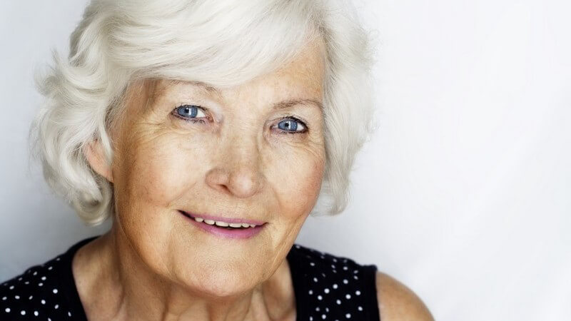 Reife Frau, Seniorin, Rentnerin, graue kurze Haare, blaue Augen, sieht fröhlich in die Kamera, trägt schwarzes Oberteil