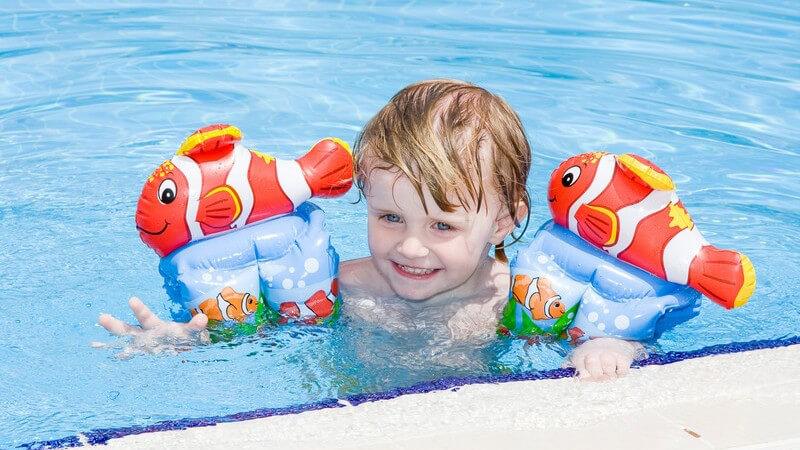 Kleines Mädchen im Swimmingpool mit Schwimmflügeln
