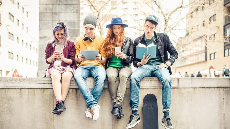 Vier Jugendliche sitzen nebeneinander auf einer Mauer und beschäftigen sich mit Smartphone, Tablet und Buch
