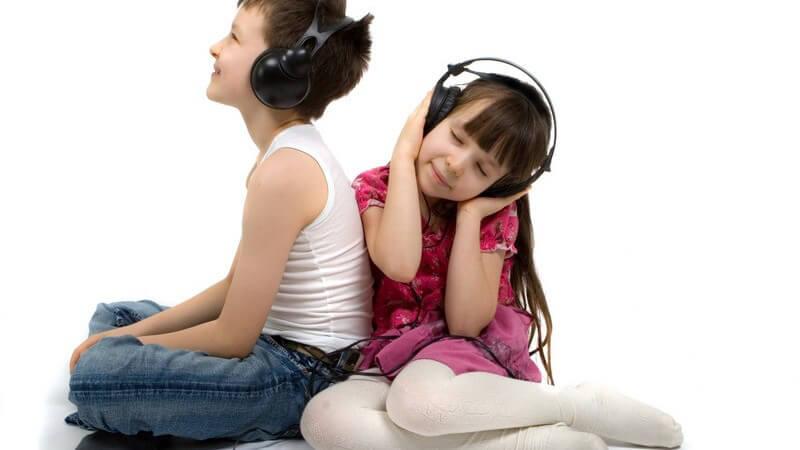 Junge und Mädchen hören Musik über Kopfhörer, weißer Hintergrund
