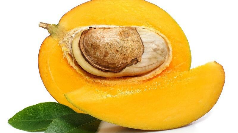 Frische halbierte Mango mit Kern und grünen Blättern auf weißem Hintergrund
