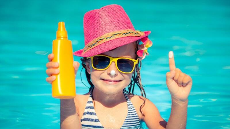 Mädchen mit pinkem Sonnenhut im Pool, hält eine gelbe Sonnencremeflasche hoch