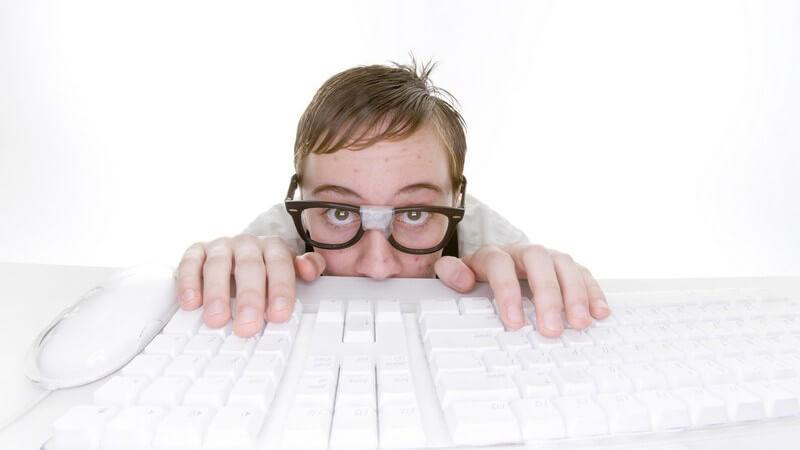 Schüchternder Computerfreak mit kaputter Brille sitzt an seiner Tastatur