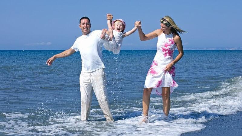 Familie am Strand, Vater in weiß, Mutter in weiß-pinkem Kleid, mit Tochter o. Mädchen in der Mitte in Wasser bei Sonne